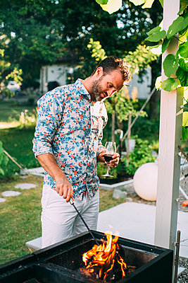 Man barbecuing in garden - p312m1557111 by Anna Rostrom
