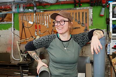 Female plumber working in workshop - p312m2262886 by Phia Bergdahl