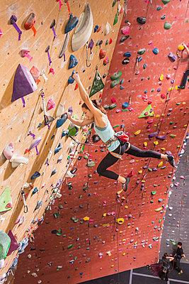 Caucasian woman climbing rock wall - p555m1312141 by Don Mason