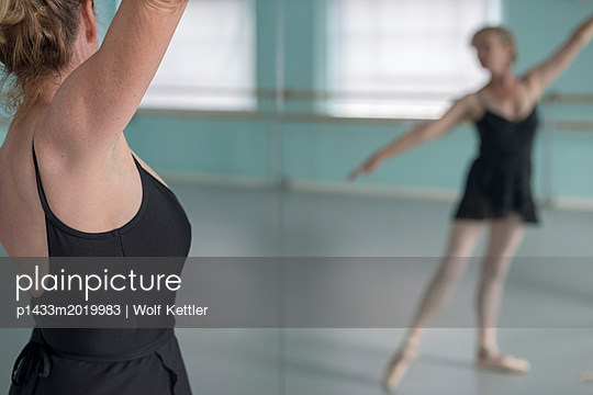 A middle-aged ballet dancer practises before a mirror. - p1433m2019983 by Wolf Kettler