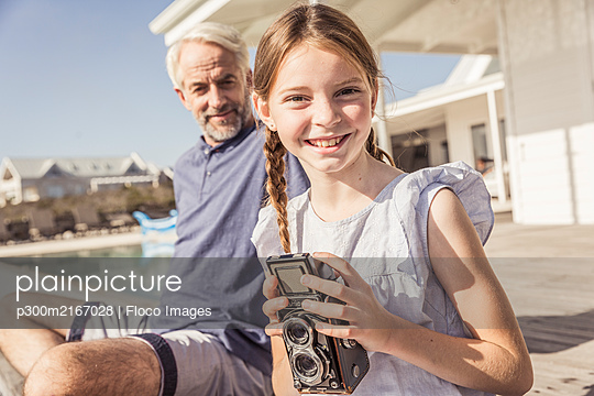 Portait of smiling girl sitting on terrace in sunshine with vintage camera - p300m2167028 by Floco Images