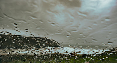 Coastline during a storm as rain settles on a car windscreen gradually obscuring the view. - p1057m2089714 by Stephen Shepherd
