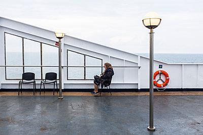 Alte Frau sitzt auf einem Schiffsdeck - p280m1111792 von victor s. brigola