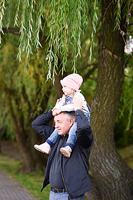 Grandfather carrying granddaughter on shoulders against tree in park - p300m2251366 by Ekaterina Yakunina