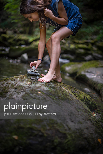 Girl stacking stones on the riverbank - p1007m2220003 by Tilby Vattard