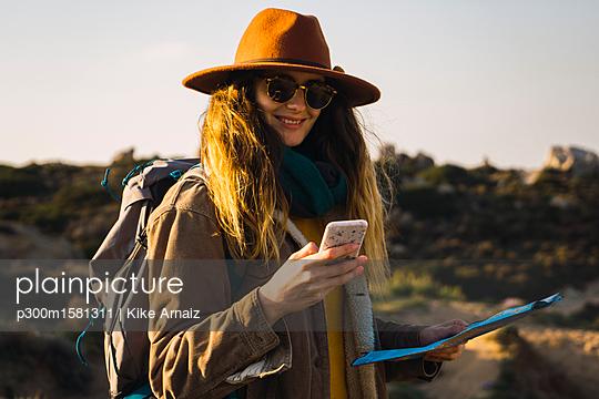 Italy, Sardinia, smiling woman on a hiking trip holding cell phone and map - p300m1581311 von Kike Arnaiz