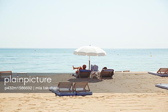 Älteres Paar sonnt sich am Strand von Saint Tropez - p432m1586692 von mia takahara