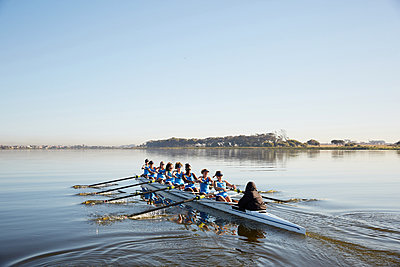 Female rowing team rowing scull on tranquil lake - p1023m1575821 by Richard Johnson