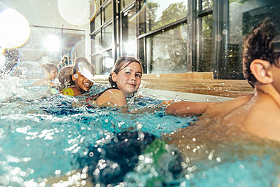 Children in swimming class practicing at poolside in indoor swimming pool - p300m1535313 by Mareen Fischinger