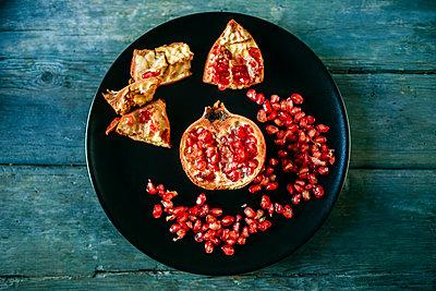Half of pomegranate and pomegranate seed on black plate - p300m1535897 by Kiko Jimenez