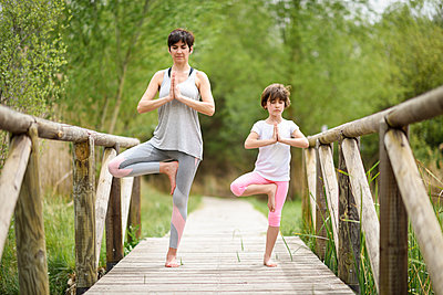 Mother and daughter doing yoga on boardwalk - p300m1587967 by Javier Sánchez Mingorance