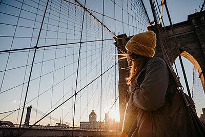 USA, New York, New York City, female tourist on Brooklyn Bridge at sunrise - p300m2081050 by letizia haessig photography