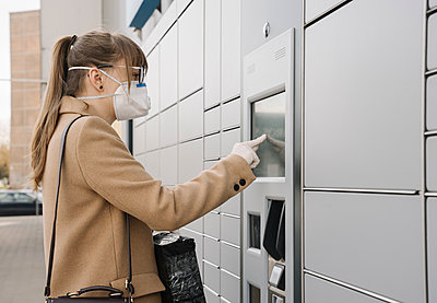 Woman wearing face mask and gloves using parcel terminal - p300m2188114 by Hernandez and Sorokina