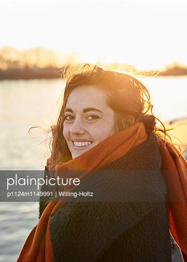 Junge Frau am Wasser im Gegenlicht - p1124m1149991 von Willing-Holtz