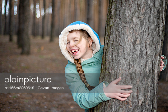 Teen girl looking out from behind the tree in the forest and laughing - p1166m2269619 by Cavan Images