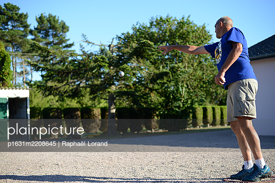 Man playing petanque in West of France - p1631m2208645 by Raphaël Lorand