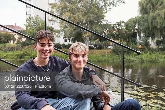 Two teenage boys sitting together - p312m2237320 by Plattform