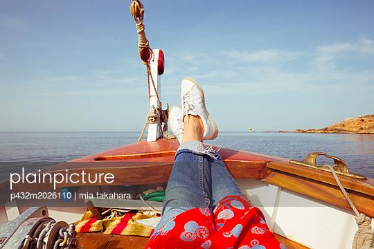 Frau streckt auf Boot Beine aus - p432m2026110 von mia takahara