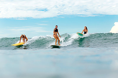 Group of female surfers riding the wave - p1108m1296591 by trubavin