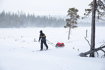 Man on backcountry skiing hike pulling a ski pulk (toboggan) - p1687m2278796 by Katja Kircher