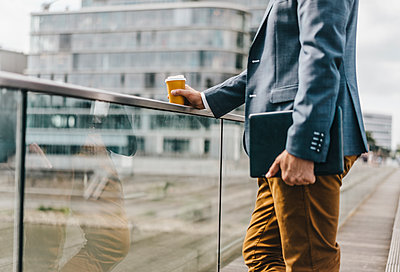 Businessman standing on bridge with coffee and tablet - p300m1175852 by Kniel Synnatzschke