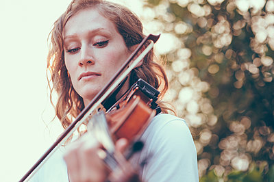 Close-up of young woman playing violin - p301m1498851 by Jay Delaney