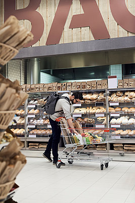 Man keeping paper bag in shopping cart while standing by bread rack at supermarket - p426m1451877 by Maskot