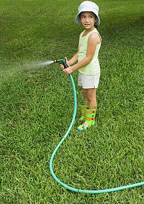 Little girl standing with garden hose - p6238063f by Michele Constantini
