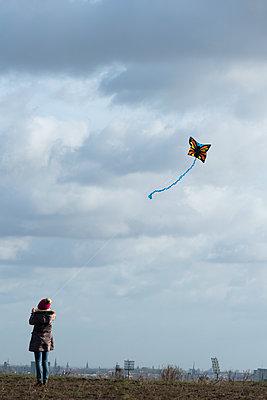 Mädchen lässt einen Drachen steigen - p739m1185391 von Baertels