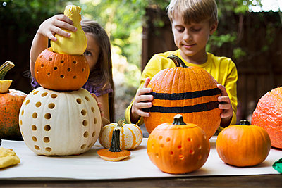 Girl and brother stacking carved pumpkins on garden table - p924m1469001 by Kinzie Riehm