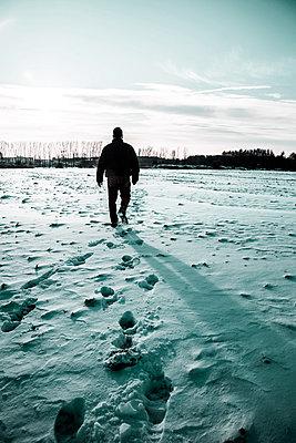 Man Walking in Snow - p975m966773 by Hayden Verry