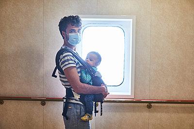 Vater mit Schutzmaske und Baby, Portrait - p1146m2231322 von Stephanie Uhlenbrock