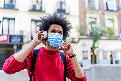 young man with afro hair listening to music from his smartphone - p1166m2255132 by Cavan Images