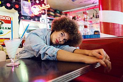Junge Frau mit Afro in American Diner - p1301m1467394 von Delia Baum