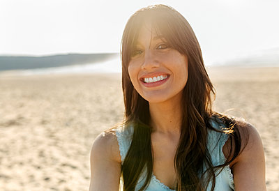 Portrait of a smiling young woman on the beach - p300m2114712 by Marco Govel