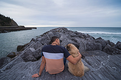 Man with arm around dog while sitting on rock against sky - p300m2256627 by SERGIO NIEVAS