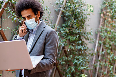 Afro businessman wearing protective face mask holding laptop while talking on smart - p300m2275279 by Ignacio Ferrándiz Roig