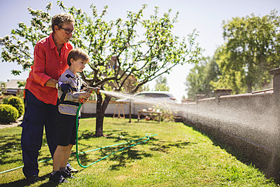 Full length of grandmother assisting grandson in spraying water on surrounding wall at yard - p426m1468451 by Maskot