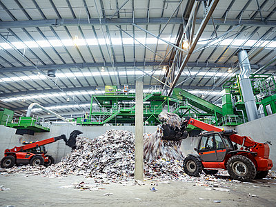 Diggers with waste paper in waste recycling plant. - p429m2202293 by Monty Rakusen