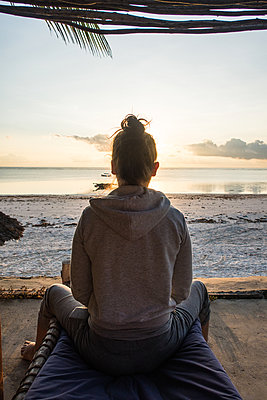 Young woman watching sunrise by the sea - p930m1541598 by Ignatio Bravo