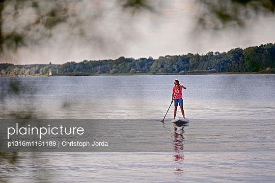 Frau beim Stand Up Paddling auf dem Chiemsee, Chiemgau, Bayern, Deutschland - p1316m1161189 von Christoph Jorda