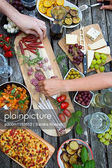 People enjoying variety of Mediterranean antipasti - p300m1153812 by Sandra Roesch