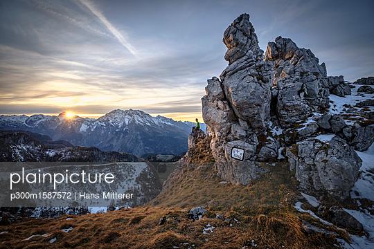 Germany, Bavaria, Berchtesgaden Alps, View to Schneibstein, hiker sitting on viewing point at sunset - p300m1587572 von Hans Mitterer
