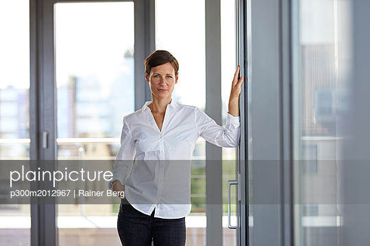Portrait of confident businesswoman standing in office - p300m2012967 von Rainer Berg