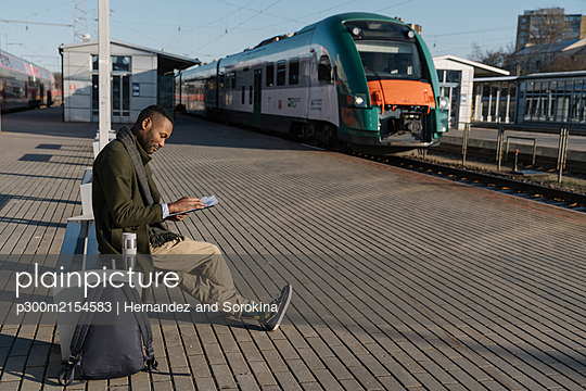 Stylish man reading documents while waiting for the train - p300m2154583 by Hernandez and Sorokina