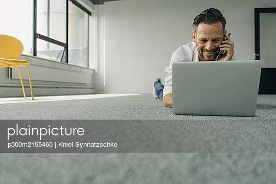 Smiling mature businessman lying on the floor in empty office using laptop and smartphone - p300m2155460 by Kniel Synnatzschke