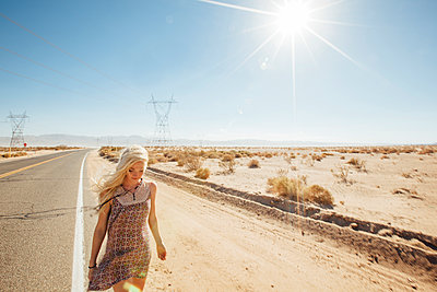 Woman walking on road by desert during sunny day - p1166m1227796 by Cavan Images