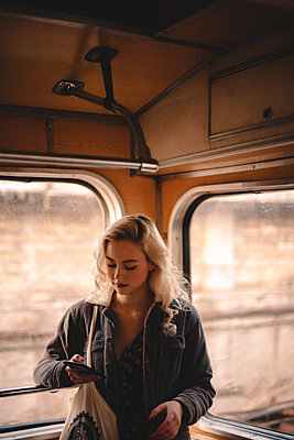 Young woman using smart phone while traveling in subway train - p1166m2153484 by Cavan Images