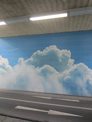 Road with directional arrows and clouded sky on tunnel wall - p1590m2224817 by marion blomeyer