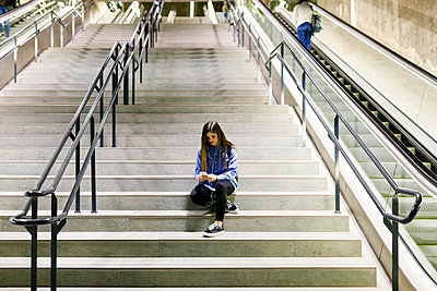 Young woman sitting on stairs using cell phone and earphones - p300m1587730 von Valentina Barreto